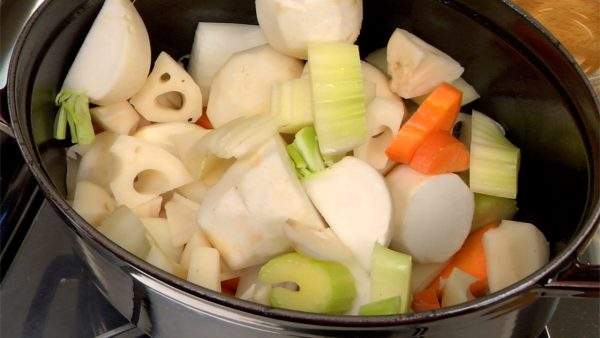 Remove the remaining oil with a paper towel. Add the olive oil and turn on the burner. To the heated pot, add the carrot, onion, lotus root, satoimo taro, turnip and celery. Lightly stir-fry the vegetables with a pair of tongs.