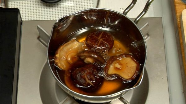Put the shiitake into a small pot and pour in the liquid. Turn on the burner.