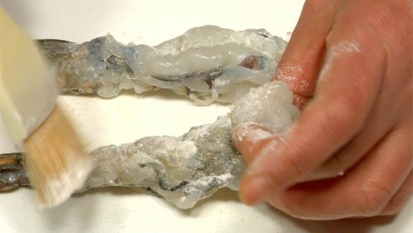 Let's make prawn tempura. Sprinkle on salt and brush tempura flour onto the prawn.