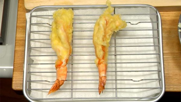 When the bubbles get small and the tempura becomes crispy, remove the prawn. Shake off a bit of the excess oil and place the prawns on a cooling rack.