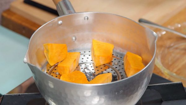 Let's prepare the kabocha squash also known as Japanese pumpkin. Place the kabocha into a steamer and turn on the burner.