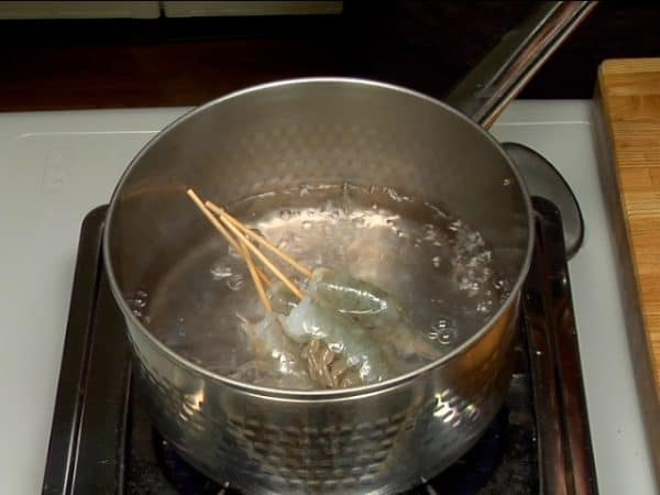 Let's cook the prawns. Add salt in a pot of boiling water. Place the prawns with a bamboo skewer in boiling water