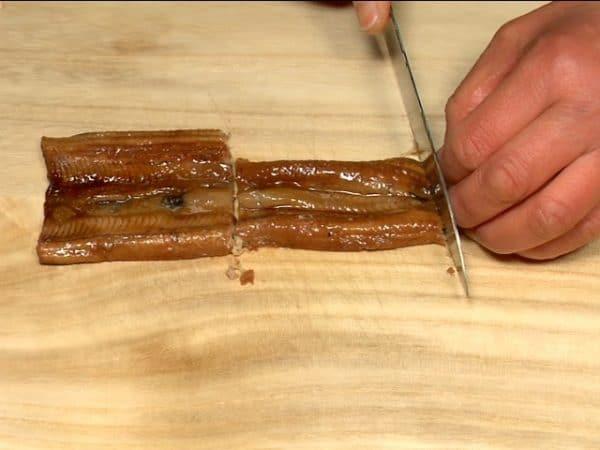 """Chop the anago, conger eel into three pieces. Cut it into 1cm (0.4"""") pieces."""