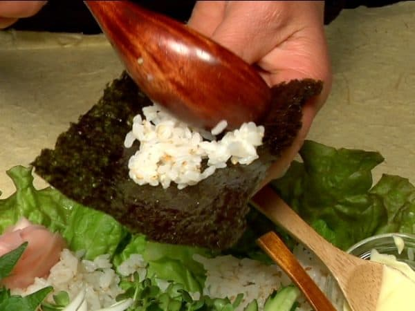 Here is an example of how to eat Temaki Sushi. Place a small amount of the sushi rice on a sheet of toasted nori.