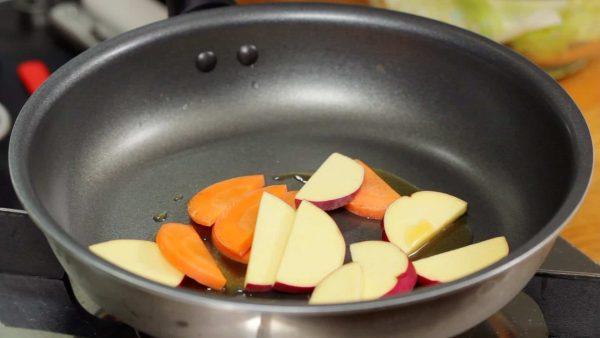 ではチーズタッカルビを焼きます。フライパンを熱しごま油を入れます。さつまいも、人参を炒めます。