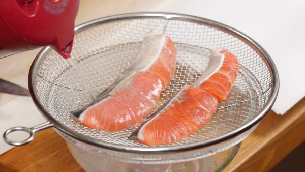 Pour hot water over the skin of the salmon. This will make it easy to remove the scales and also get rid of the fishy odor.