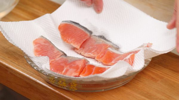 Rinse the fillets with water and scrub the scales off. Place the salmon onto a paper towel and remove the moisture.