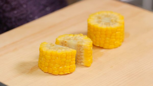 "Cut the boiled ear of corn into 3cm (1.2"") pieces. Then, cut each into half moons."