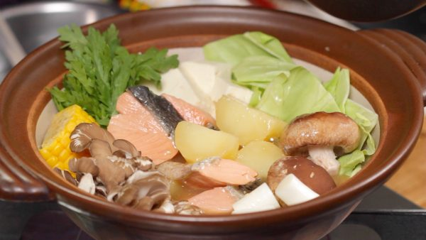 Arrange the salmon and the potato along with the vegetables in the pot. And ladle in the broth.
