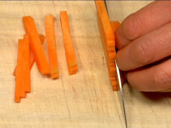 "Slice the carrot into 5mm (0.2"") slices. Stack the layers and chop them into 5mm (0.2"") strips."