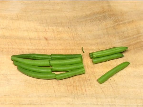 "Chop off the stem ends of green beans. Trim off the other ends of the beans. Cut the green beans into 5cm (2"") pieces."