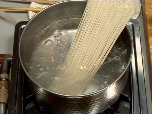 Place a bundle of soba noodles in a large pot of boiling water. Gently separate the noodles evenly in boiling water.
