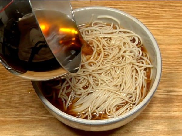 Transfer the noodles to the preheated bowl. Pour the hot noodle soup on the soba noodles.