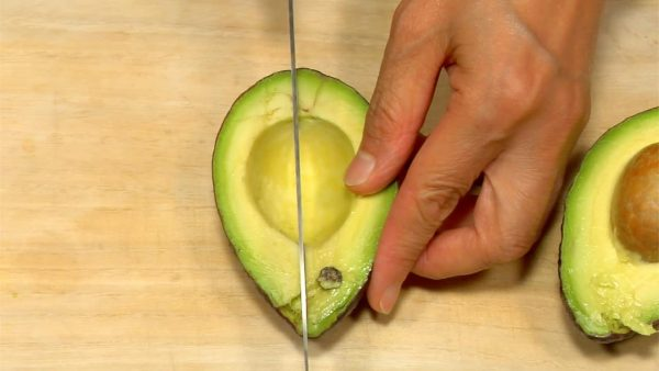 Cut the avocado lengthwise around the seed. Twist, and split it in half. Cut it into quarter wedges.