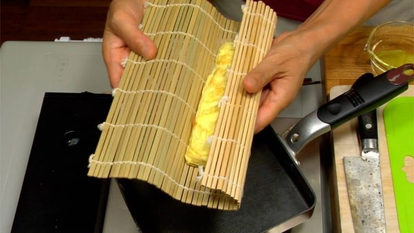 Take a bamboo mat and flip the pan over it. Shape the omelet, and let it cool down.