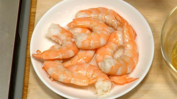 Pour one half tablespoon sushi vinegar onto the pre-boiled shrimp. Flip them over to marinate evenly.