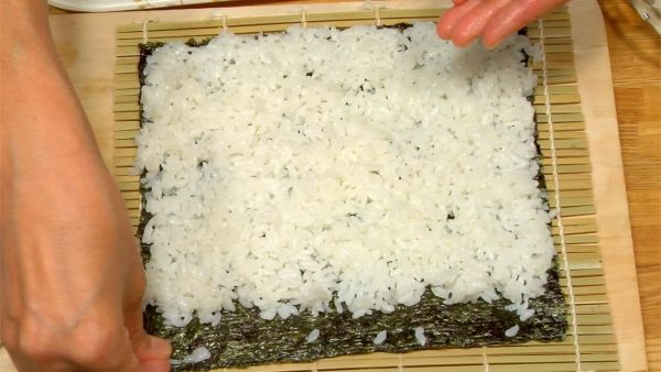 Put some rice-grains on the margin...these will hold the piece together when it is rolled with the fillings inside.