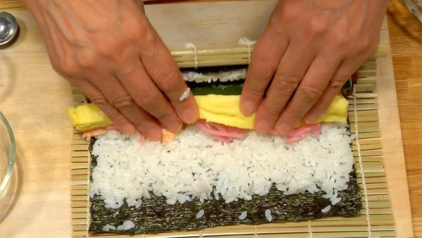 Carefully lift the edge of the mat and roll the Futomaki while holding down the fillings.