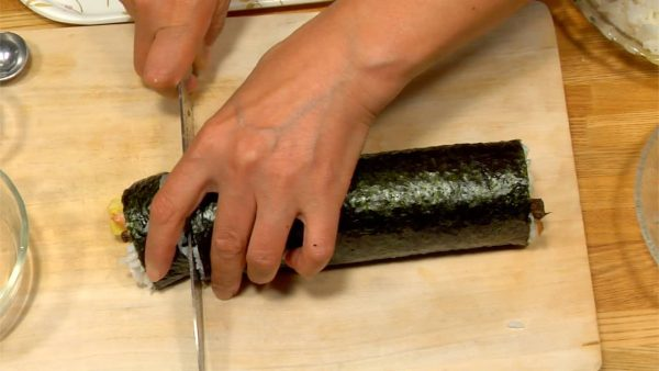 Wet both sides of a knife and cut off both ends of the Futomaki. Wipe the knife with a wet towel between every cuts to stop the rice sticking to the blade. You'll get 8 pieces of Futomaki in total.