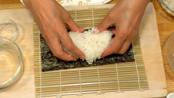 Next, let's make California Roll. Place the half size nori on the mat. Wet your hands with vinegar water and serve the measured rice on the nori. Cover with a layer of rice evenly.