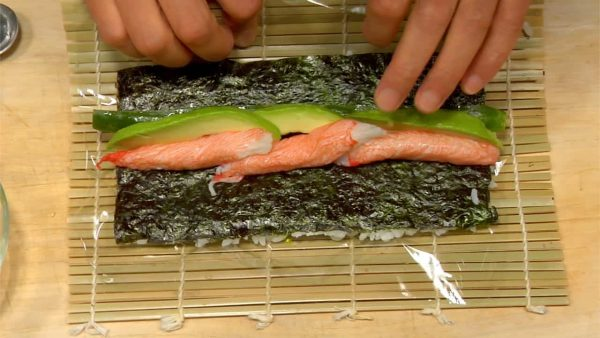 Place the cucumber on the center of the nori. Line up the avocado and crab sticks. Lift the edge of the mat and roll it while holding down the fillings.