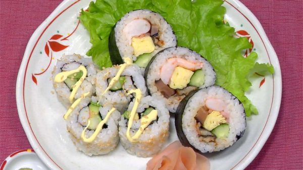 Serve the Futomaki Sushi and California Roll on a dish. Garnish with the pickled ginger and mustard greens. Finally, top the California Roll with mayonnaise.