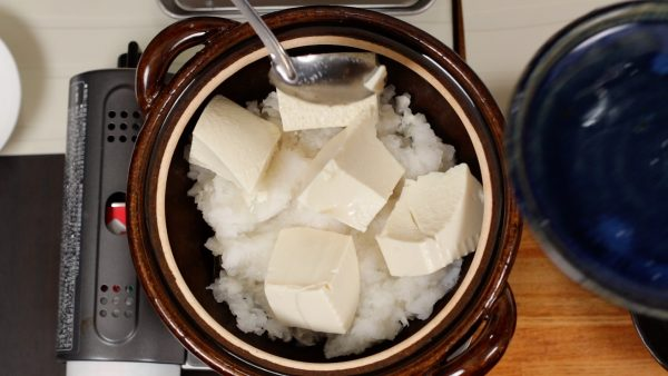 Next, place the soft silken tofu onto the daikon. Divide the tofu into 4 to 5 pieces but be sure not to break them.