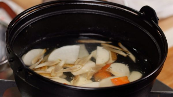 And now, let's make the dango-jiru. Heat the niboshi dashi stock in a pot. And add the parboiled root vegetables.