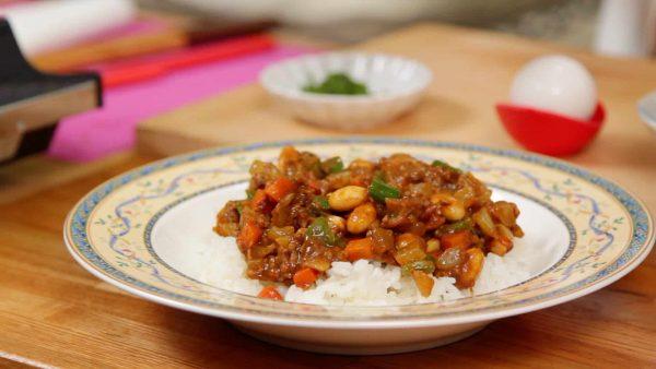 Và bây giờ, để cơm mới nấu lên đĩa. Múc cà ri khô lên cơm. Sau đó, tạo một lỗ nông ở trên.