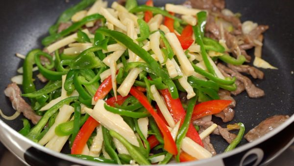 When the beef is almost cooked, add the bell pepper and bamboo shoot.