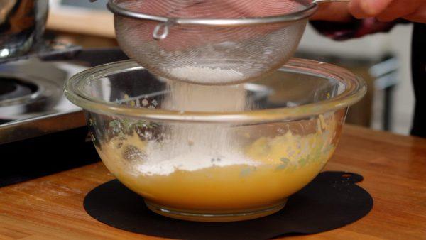 ボウルにざるをかけ薄力粉、コーンスターチを加えます。ふるいにかけ卵黄に加えしっかり混ぜます。
