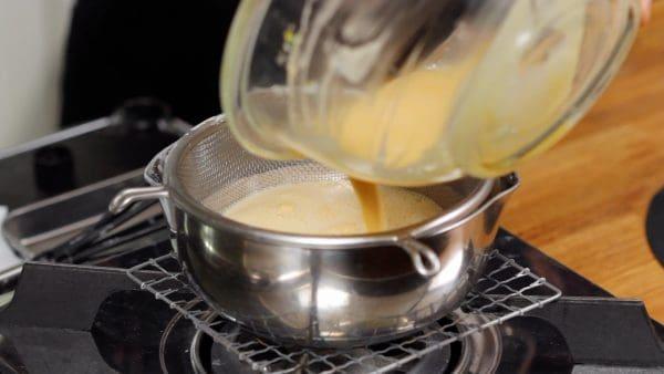 鍋にザルをかけ、卵液をざるでこしながら鍋に戻します。カラザやダマを取り除き、滑らかに仕上げるためです。