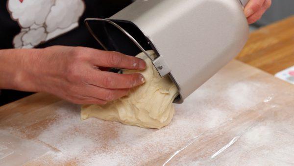 こね台には薄く手粉(強力粉)を振り、ホームベーカリーの蓋を開け容器を取り出します。手に粉をつけ生地を台に取り出します。もう一度生地に軽く粉をつけます。