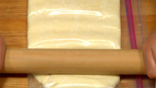 Gradually shift the rolling pin, and spread the dough until the bag is filled.