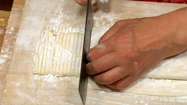 Position the knife vertically to the creases and cut the dough into noodles.