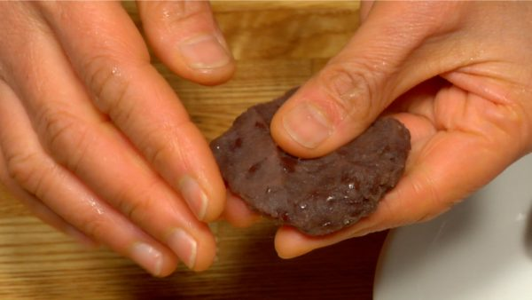 With your fingers, shape a piece of anko so it's flat and round.