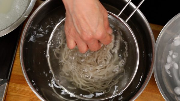 Then, submerge the noodles in a large amount of water to cool and lightly rub them to remove the gooey texture on the surface. We are demonstrating every step on this counter, but you should rinse them thoroughly with running water.