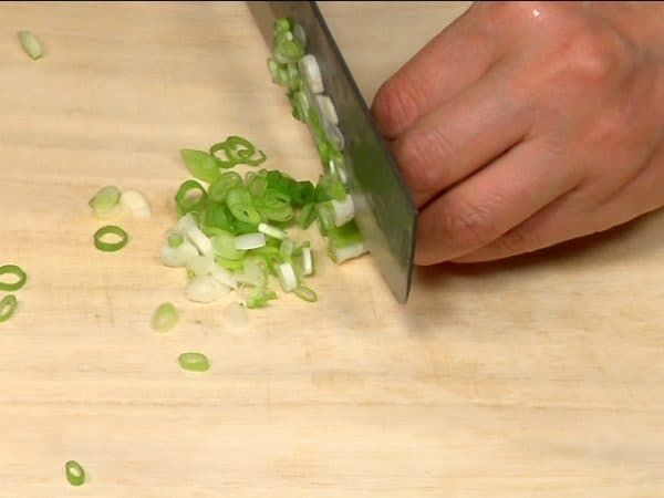 Let's prepare the fillings. Chop the spring onion leaves into fine pieces.