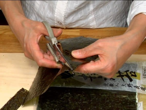 With kitchen shears, cut the toasted nori seaweed into one short strip, two triangles and one long strip.