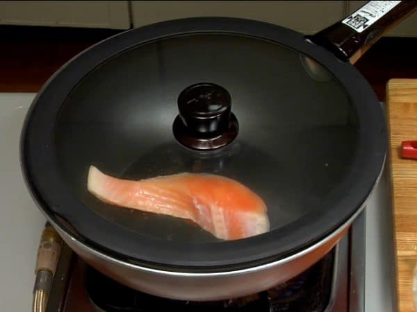 Next, place the lightly-salted salmon fillet into the pan and cover with a lid.