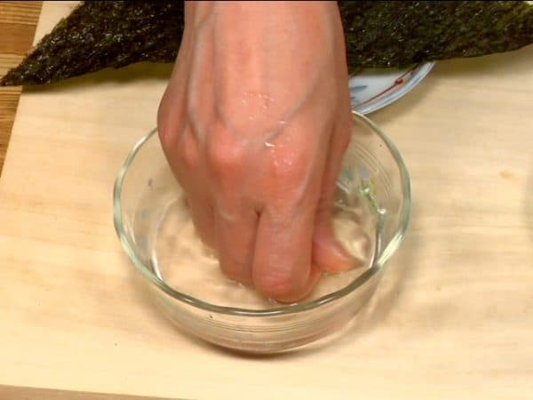 Let's make the salmon onigiri. Wet your hands with the salt water to prevent the rice from sticking.