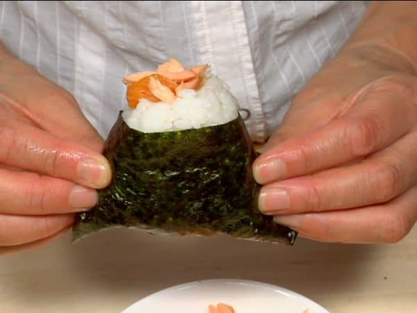 Make a shallow hole in the top corner of the onigiri and fill with the salmon.