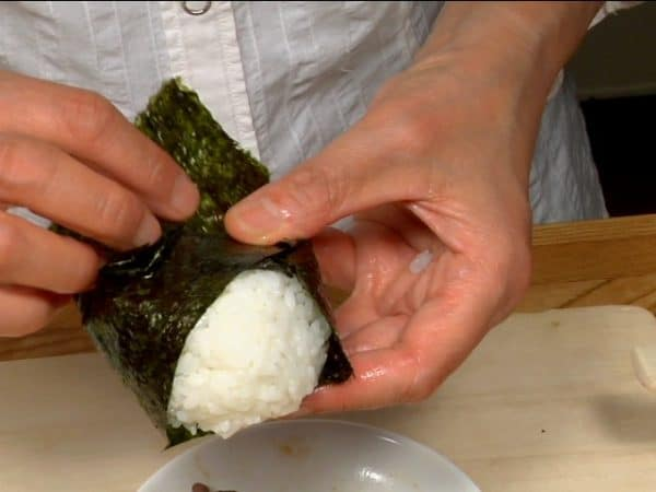 Wrap the onigiri with the triangular nori.