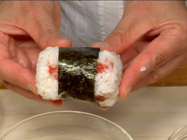 Wet your hands with the salt water and form the rice into a cylinder. Wrap the onigiri with the strip of nori.