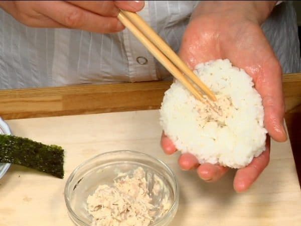 For the tuna mayonnaise onigiri, place the tuna mayo onto the rice and shape the onigiri into a flat round shape.