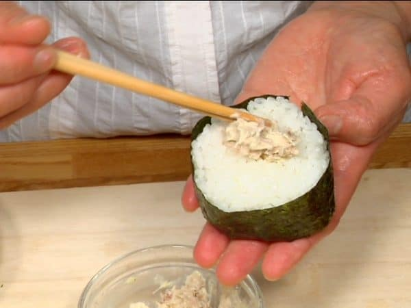 Wrap the onigiri with the long strip of nori. Make a hole in the top and place the extra tuna mayo inside.