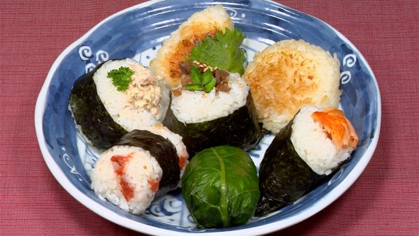 Serve the onigiri on a plate and garnish with the shiso leaf, parsley leaves, kinome leaves and white sesame seeds.