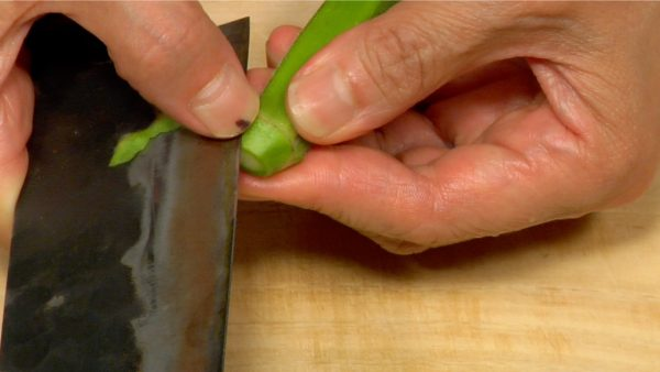 Let's prepare the side vegetables. Remove the stem ends of the pre-washed okras. Peel off the firm skins around the stem ends.