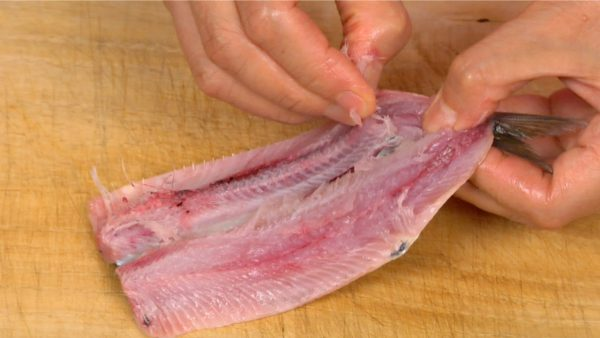 Break the backbone at the tail fin and gently peel it off the fillets.