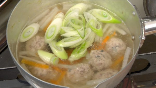 When the tsumire balls begin to float to the surface, drop in the long green onion and simmer for about 1 minute.
